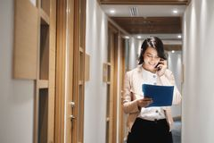 Jeune agence de Working In Financial de femme d'affaires parlant du téléphone portable image stock