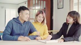 Jeune agent asiatique heureux de couples et d'agent immobilier Jeune homme gai signant quelques documents tout en se reposant au  clips vidéos