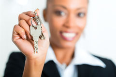 Jeune agent immobilier avec des clés dans un appartement Image stock
