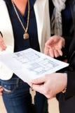 Jeune agent immobilier expliquant le plan au sol aux couples Images stock