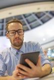 Jeune allocation des places d'homme d'affaires sur la table dans le restoran et l'utilisation De mobile Photo libre de droits