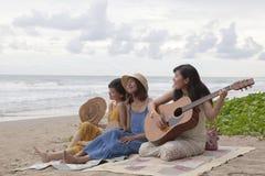 Jeune ami asiatique de femme jouant la guitare sur le bonheur e de plage de mer Photo stock