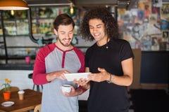 Jeune ami de sourire à l'aide du comprimé numérique dans le restaurant Images stock