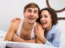 Jeune ami et amie souriant dans le lit à la maison Photos libres de droits
