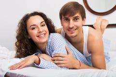 Jeune ami et amie souriant dans le lit à la maison Photographie stock libre de droits