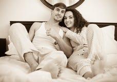 Jeune ami et amie souriant dans le lit à la maison Photographie stock