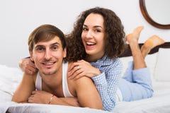 Jeune ami et amie souriant dans le lit à la maison Photo libre de droits