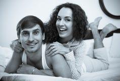 Jeune ami et amie souriant dans le lit à la maison Photos stock