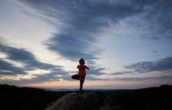 Jeune amincissez la femme convenable faisant des exercices de yoga se tenant nu-pieds sur une jambe sur la grande roche de montag Photo libre de droits