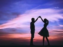 Jeune amour de couples au coucher du soleil Photo stock