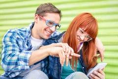 Jeune amusement heureux des couples 0having avec le smartphone Photographie stock libre de droits