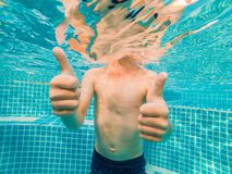 Jeune amusement sous-marin de garçon dans la piscine avec des lunettes Amusement de vacances d'été photo libre de droits