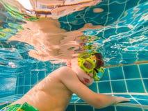 Jeune amusement sous-marin de garçon dans la piscine avec des lunettes Amusement de vacances d'été image stock