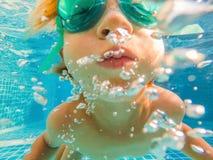 Jeune amusement sous-marin de garçon dans la piscine avec des lunettes Amusement de vacances d'été images libres de droits