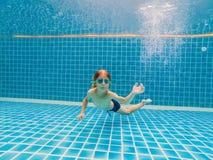 Jeune amusement sous-marin de garçon dans la piscine avec des lunettes Amusement de vacances d'été photos libres de droits