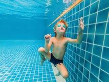 Jeune amusement sous-marin de garçon dans la piscine avec des lunettes Amusement de vacances d'été photographie stock