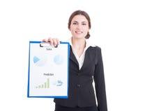Jeune apparence de femme de ventes financière et diagrammes de bénéfice sur le clipboa Photo libre de droits