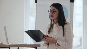 Jeune applaudissement femelle caucasien réussi heureux de haut-parleur d'entraîneur, souriant tout en présentant un exposé à l'év banque de vidéos
