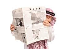 Jeune Arabe sacré se cachant derrière un journal Photos stock