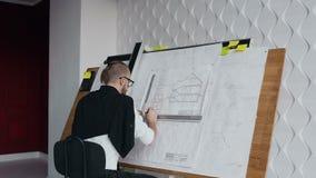 Jeune architecte masculin travaillant au dispositif de dessin un projet de modèle du nouveau bâtiment résidentiel Concept de trav banque de vidéos