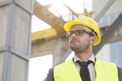 Jeune architecte masculin utilisant le casque antichoc regardant loin le chantier de construction Photographie stock