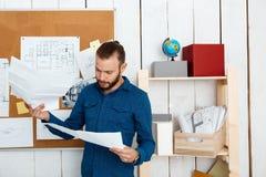 Jeune architector réussi regardant des dessins, se tenant à l'arrière-plan de bureau Photos libres de droits