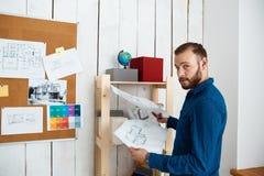Jeune architector réussi souriant, tenant des dessins, se tenant à l'arrière-plan de bureau Photos stock