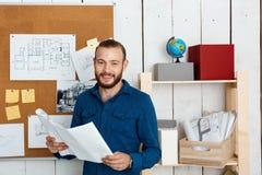 Jeune architector réussi souriant, tenant des dessins, se tenant à l'arrière-plan de bureau Image libre de droits