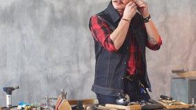 Jeune artisan essayant sur la boucle d'oreille après la réparation de elle, mâle vérifiant l'article banque de vidéos