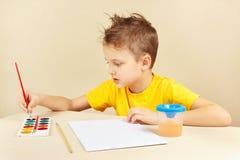 Jeune artiste dans la chemise jaune allant peindre des couleurs Photographie stock