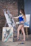 Jeune artiste féminin peignant le tableau abstrait dans le studio, beau portrait de femme Images libres de droits