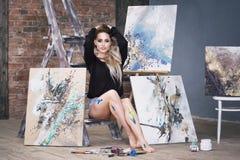 Jeune artiste féminin peignant le tableau abstrait dans le studio, beau portrait de femme Photographie stock