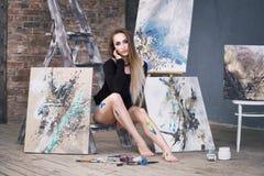 Jeune artiste féminin peignant le tableau abstrait dans le studio, beau portrait sexy de femme images stock