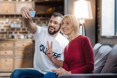 Jeune assistant social drôle prenant des photos avec un retraité Photographie stock libre de droits