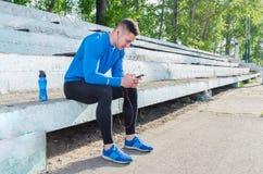 Jeune athlète écoutant la musique après la formation images stock