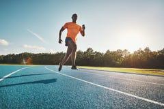 Jeune athlète africain sprintant en bas d'une voie courante photographie stock libre de droits