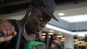 Jeune athlète afro-américain faisant l'exercice pectoral sur la machine dans le gymnase banque de vidéos