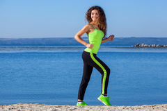 Jeune athlète avec les cheveux bouclés, le survêtement vert clair et les espadrilles fonctionnant sur la plage en été, exercice d Photos stock