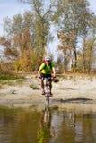 Jeune athlète croisant le terrain rocheux avec la bicyclette dans des ses mains Images libres de droits