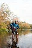 Jeune athlète croisant le terrain rocheux avec la bicyclette dans des ses mains Image stock