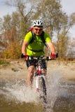 Jeune athlète croisant le terrain rocheux avec la bicyclette dans des ses mains Images stock