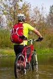 Jeune athlète croisant le terrain rocheux avec la bicyclette dans des ses mains Photographie stock libre de droits