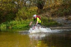Jeune athlète croisant le terrain rocheux avec la bicyclette dans des ses mains Photo stock