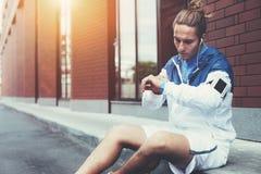 Jeune athlète dans le windrunner bleu se reposant sur la rue ajustant le programme courant pour sa séance d'entraînement de début image libre de droits
