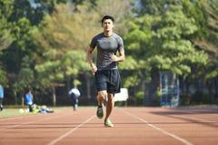 Jeune athlète masculin asiatique courant sur la voie images libres de droits