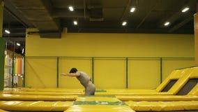 Jeune athlète masculin dans le T-shirt beige et shorts sautant à cloche-pied sur le trempoline avec la cueillette de torsion de s banque de vidéos