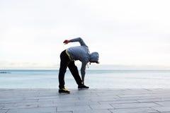 Jeune athlète masculin réchauffant après un fonctionnement intense sur la plage images stock
