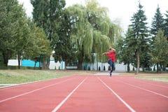 Jeune athlète masculin Running sur la voie Photographie stock