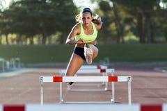 Jeune athlète sautant par-dessus un obstacle pendant la formation sur le trac de course image stock