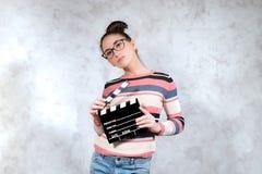 Jeune audition d'actrice posant avec le panneau de clapet de film images stock